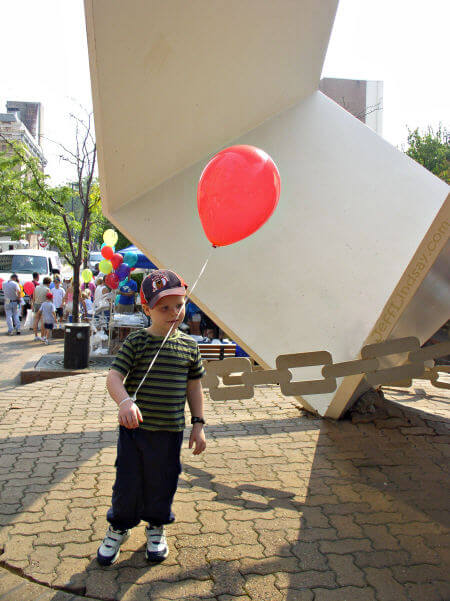 A child stands in front of the Metamorphosis sculpture on Houdini Plaza during a quiet moment at Houdini Days.