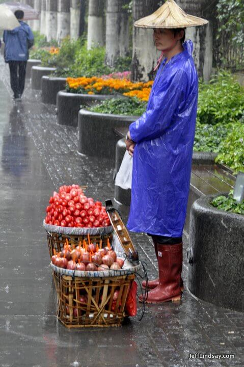 Xiamen, Fujian China, April 2013: lone fruit vendor in the rain