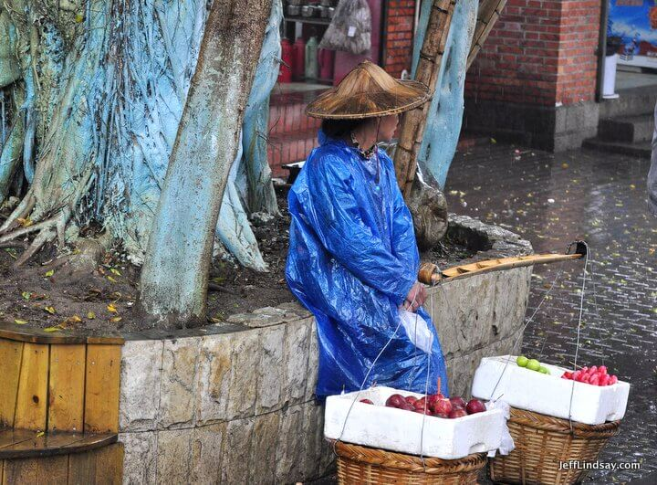 Xiamen, Fujian China, April 2013: Fruit vendor in the rain, Gulangyu Island